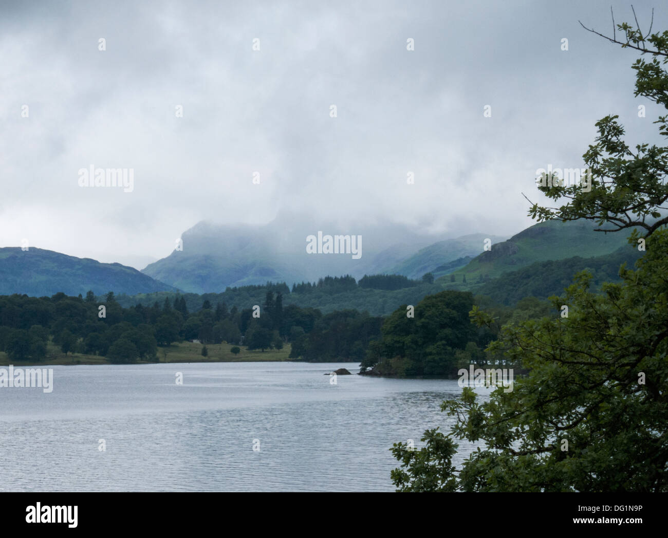 View across Lake WIndermere, with low clouds covering hills; trees in foreground. - Stock Image