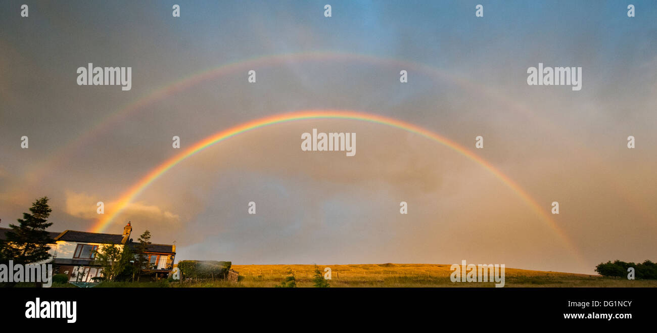 Double rainbow at sunset, against a cloudy sky over a Northumbrian dale. Stock Photo