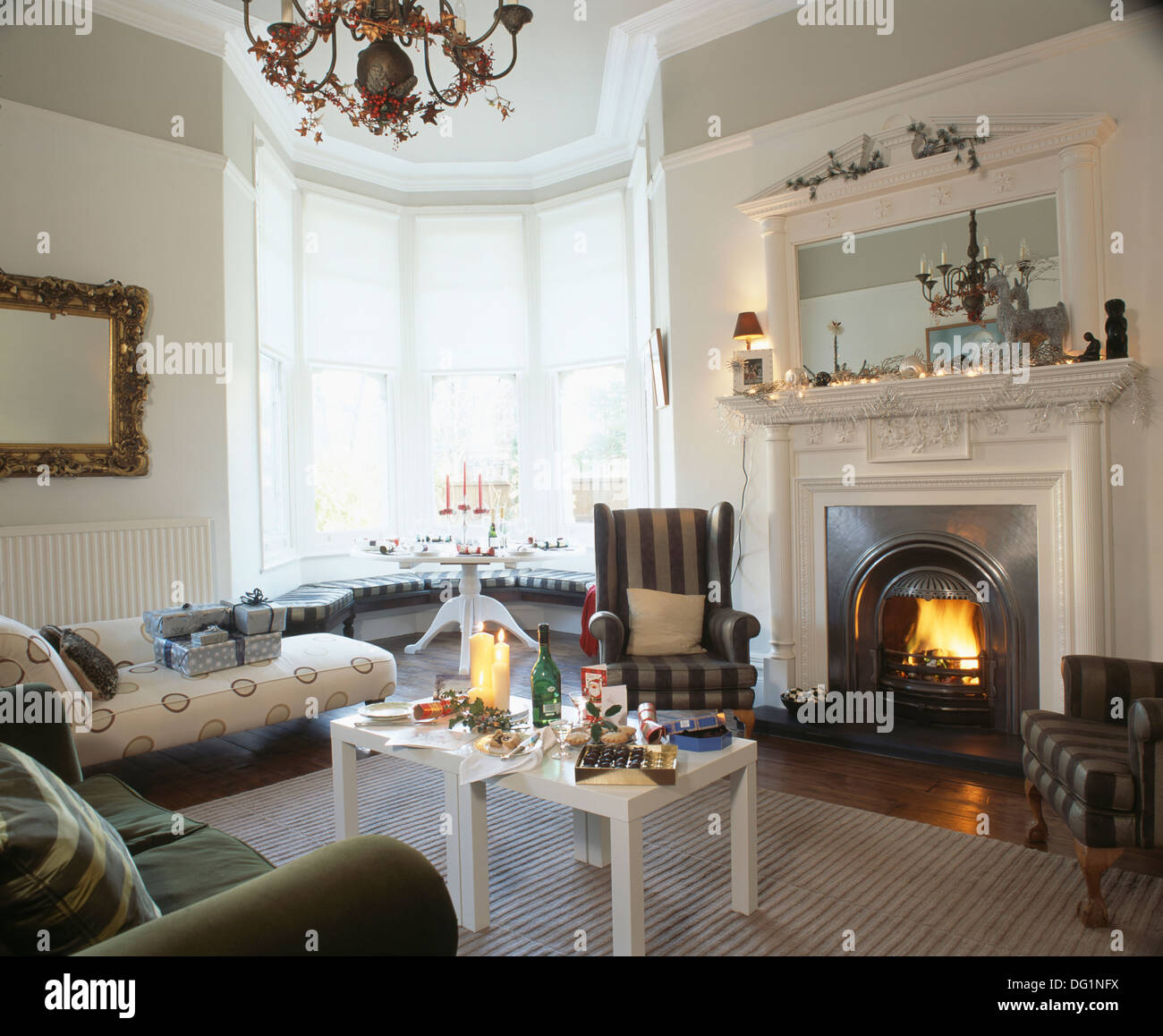 Grey striped wing chair beside fireplace below white mirror in white ...