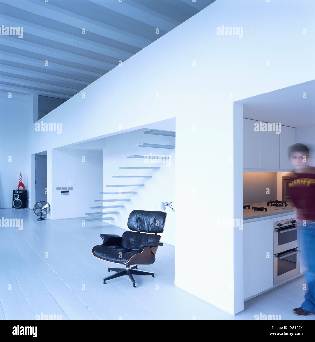 Soft focus figure standing in kitchen of large open-plan apartment with Charles Eames black leather lounge chair Stock Photo