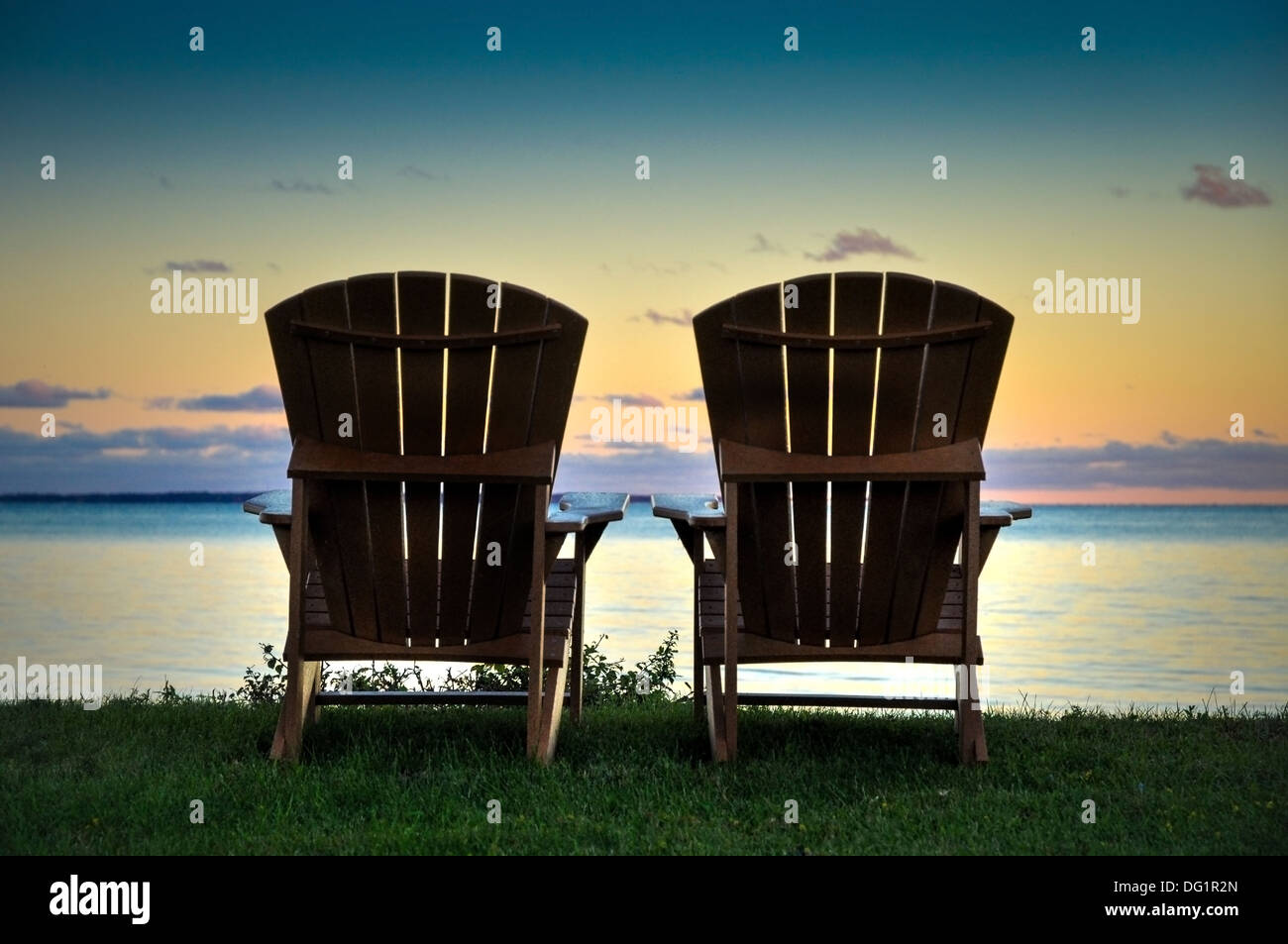 two Adirondack chairs on the shore of Lake Ontario New York usa - Stock Image