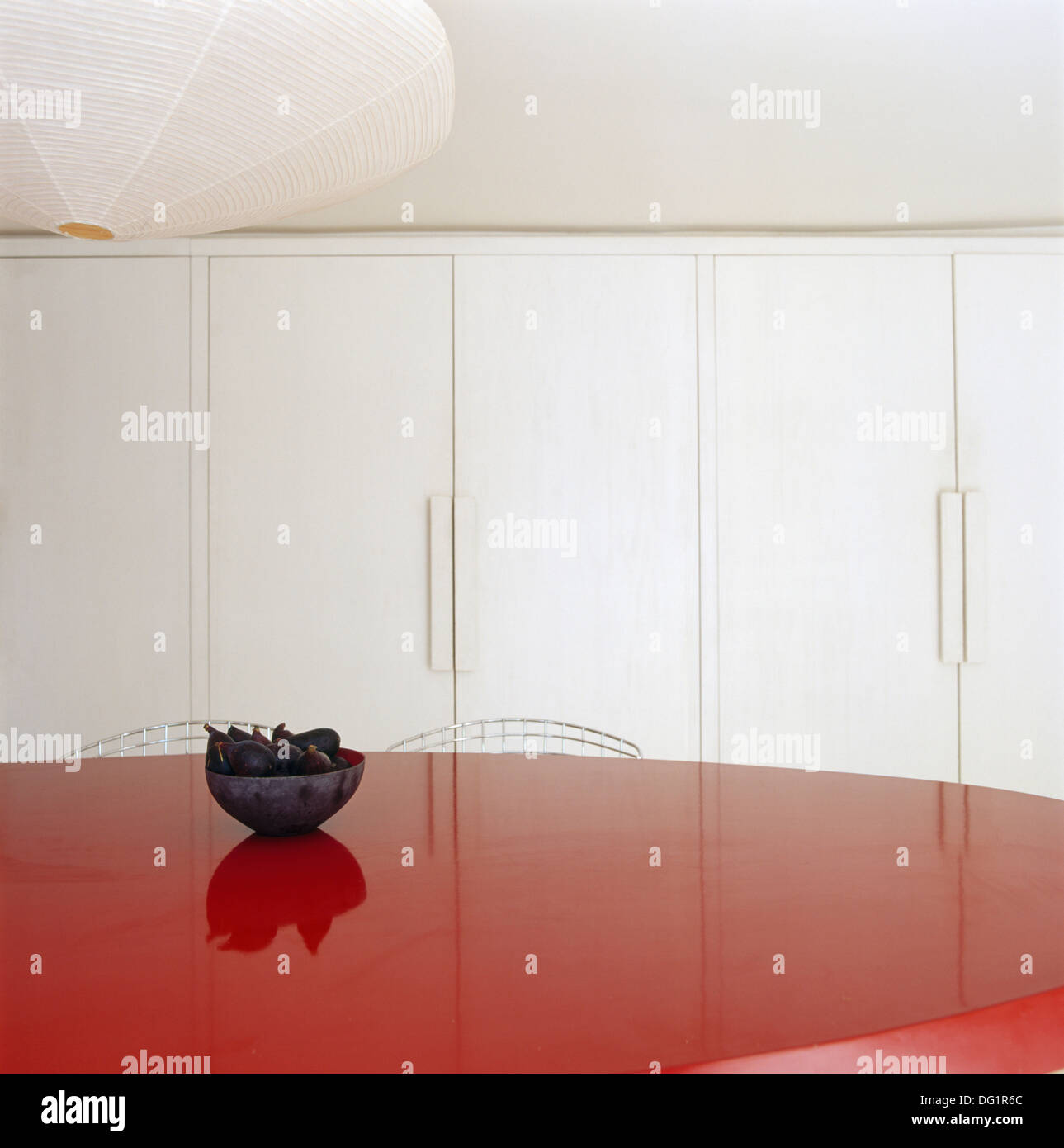 Small Bowl On Red Lacquered Table In Minimalist Dining Room With White  Fitted Storage Cupboards