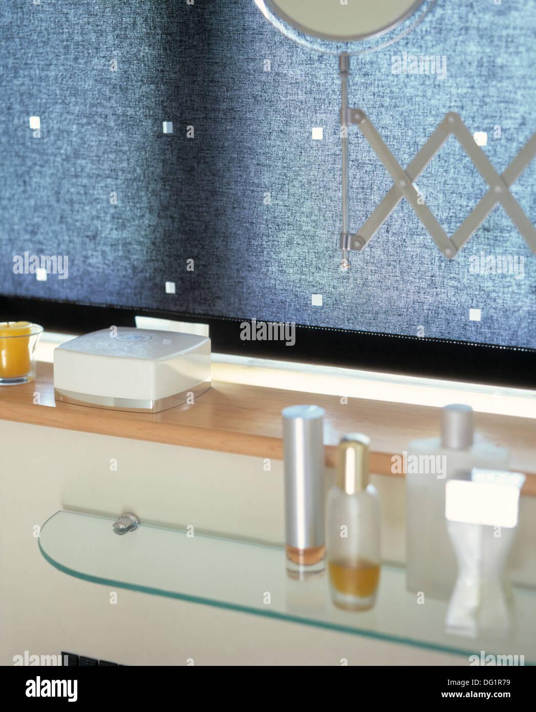 Close-up of glass bottles of toiletries on glass shelf below shelf ...