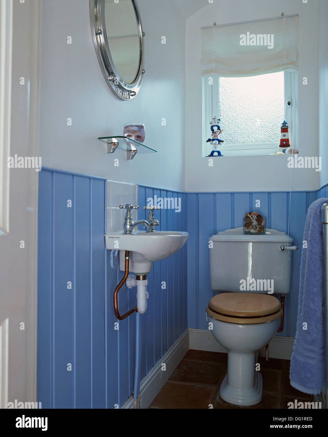Blue tongue+groove panelling in toilet with small basin and toilet ...