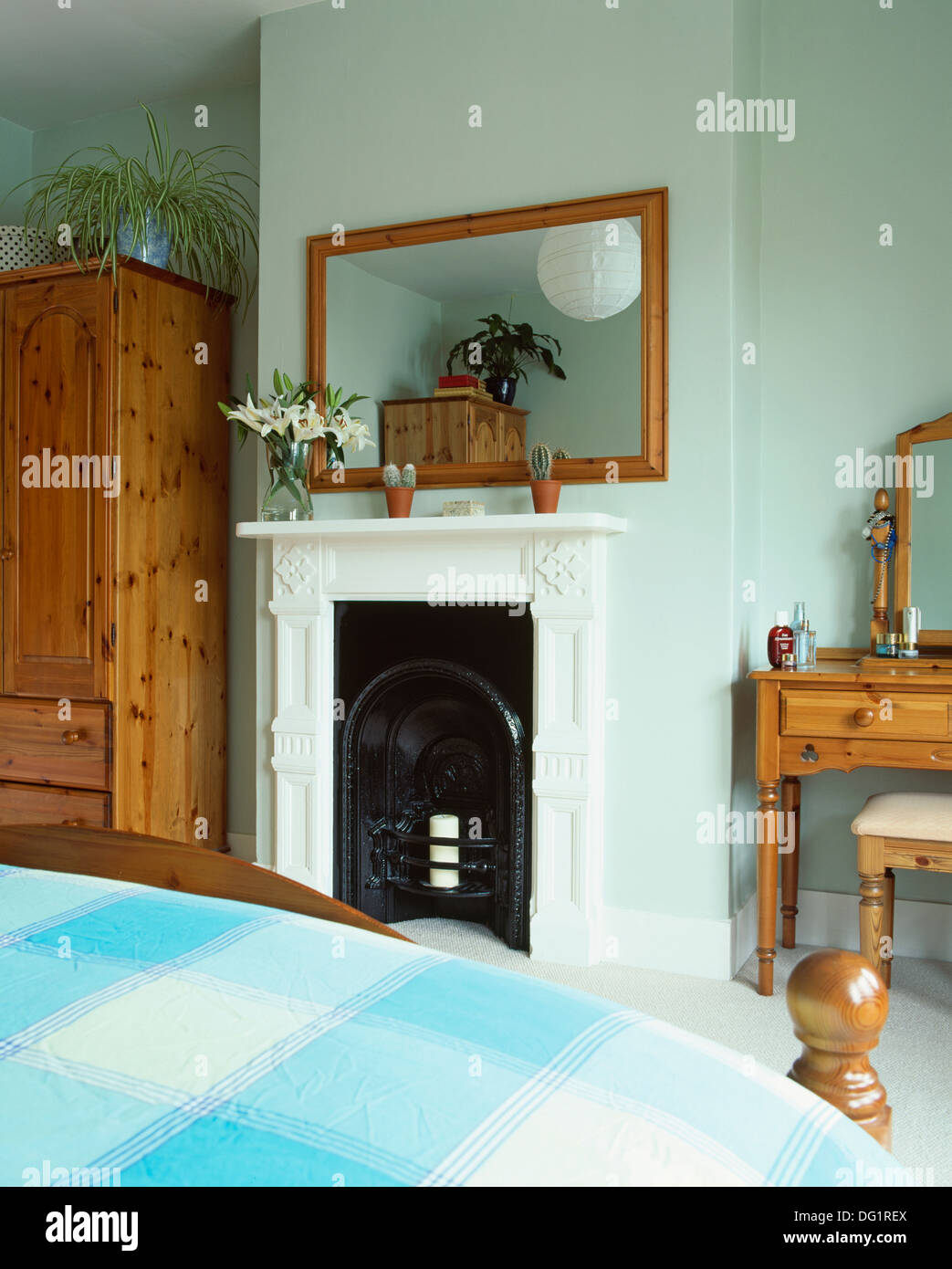 Simple wooden framed mirror above fireplace in townhouse bedroom ...
