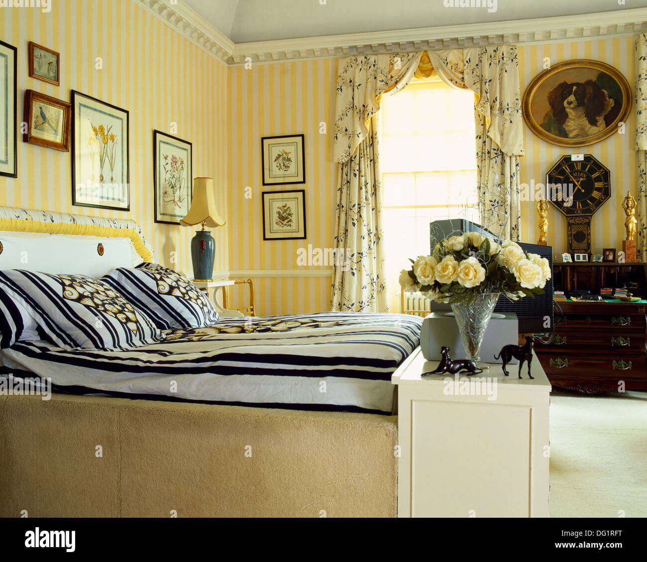 Yellow Striped Wallpaper And Floral Curtains In Townhouse Bedroom With Black +white Striped Duvet On Fitted Bed