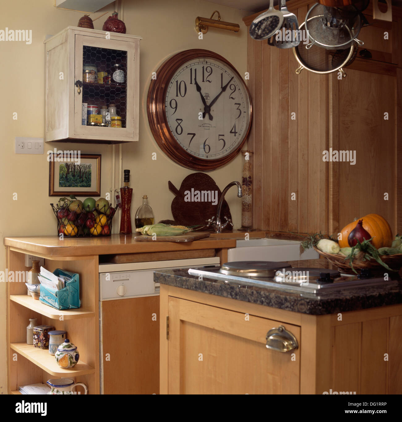Large Copper Framed Clock And Small Cupboard Above Sink In Country Stock Photo Alamy