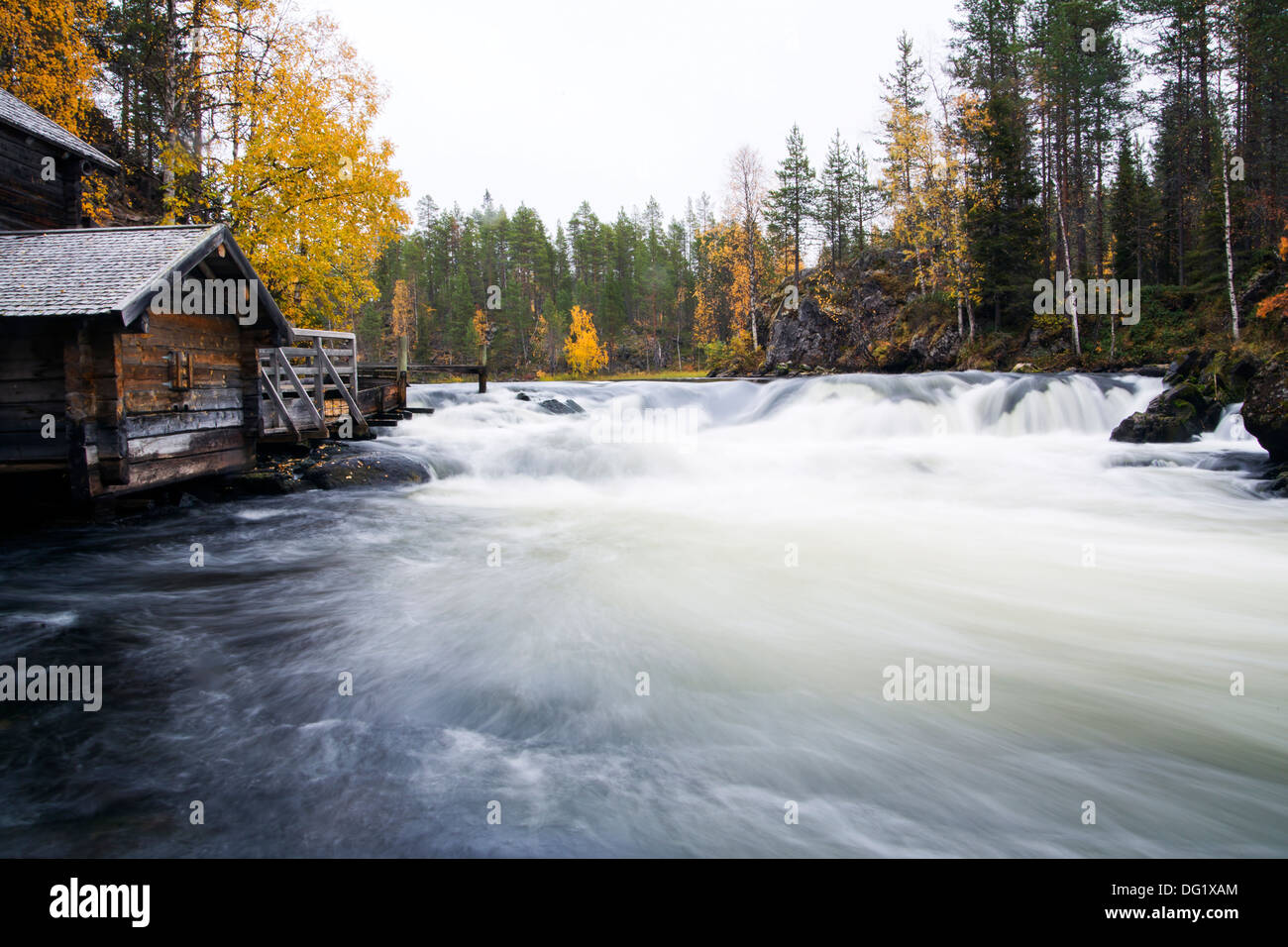 Fast flowing river flow and aged unemployed watermill - Stock Image