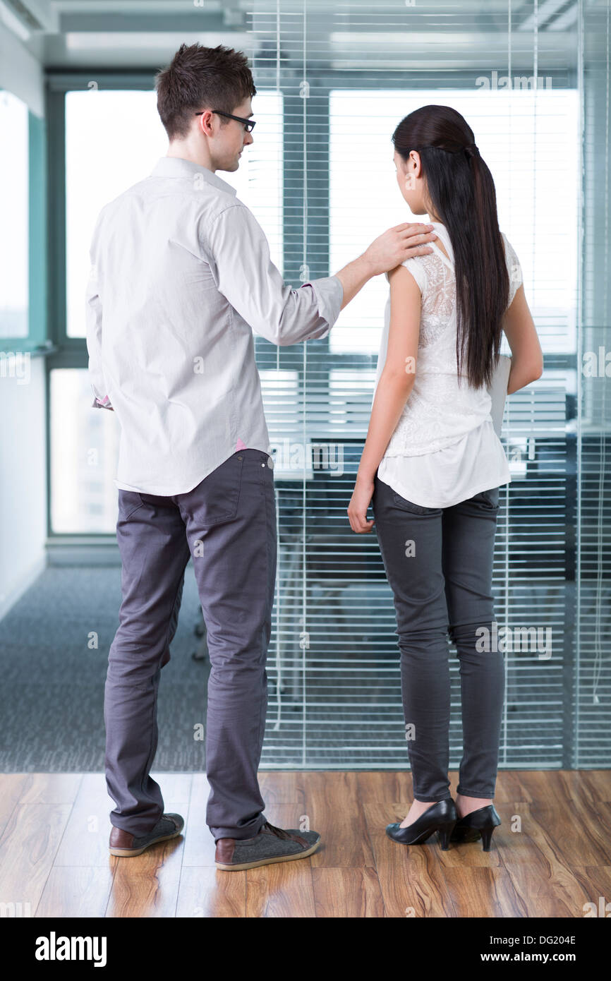 Businessman consoling his workmate - Stock Image
