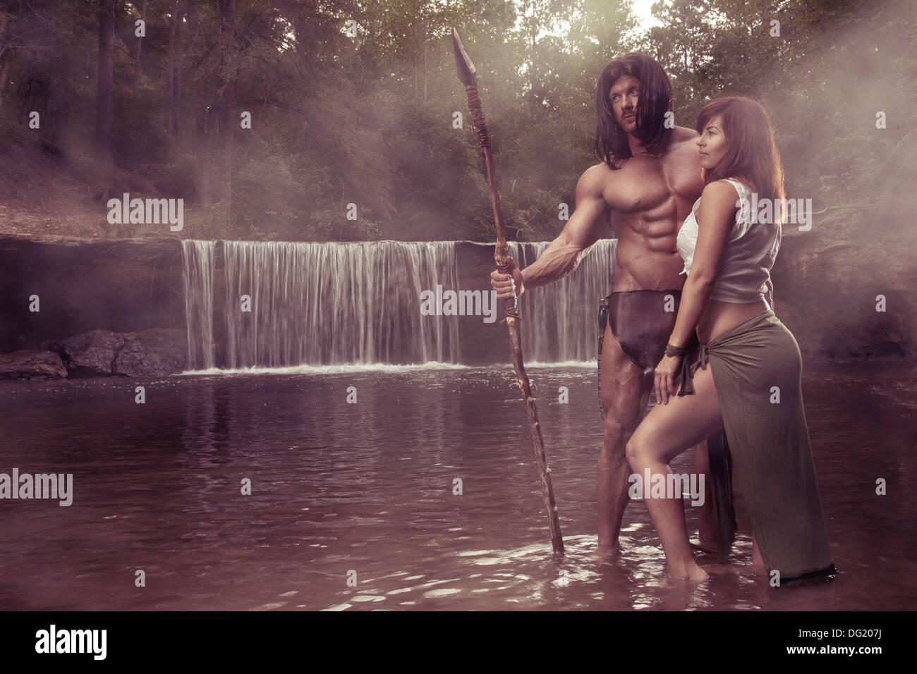 Tarzan and Jane like heroes standing in water in front of waterfall - Stock Image