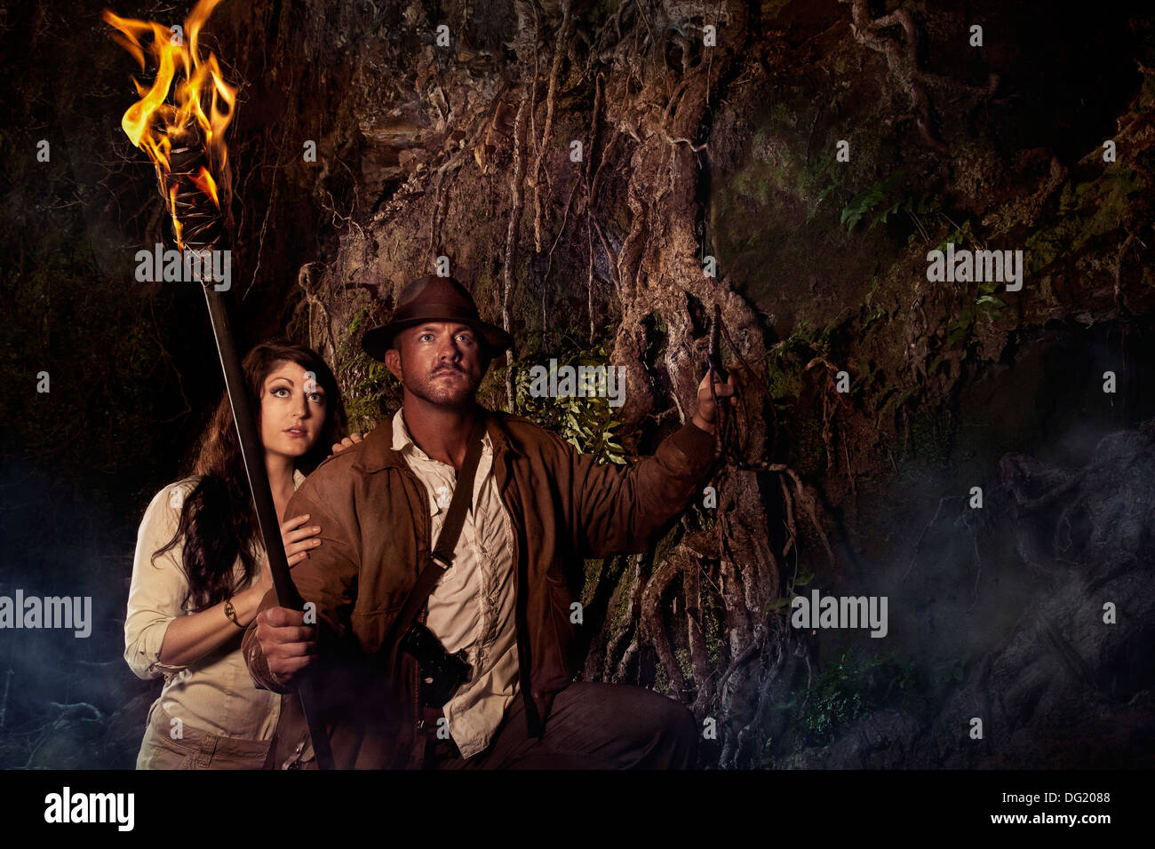 Indiana Jones styled adventure hunter in cave with woman carrying torch - Stock Image
