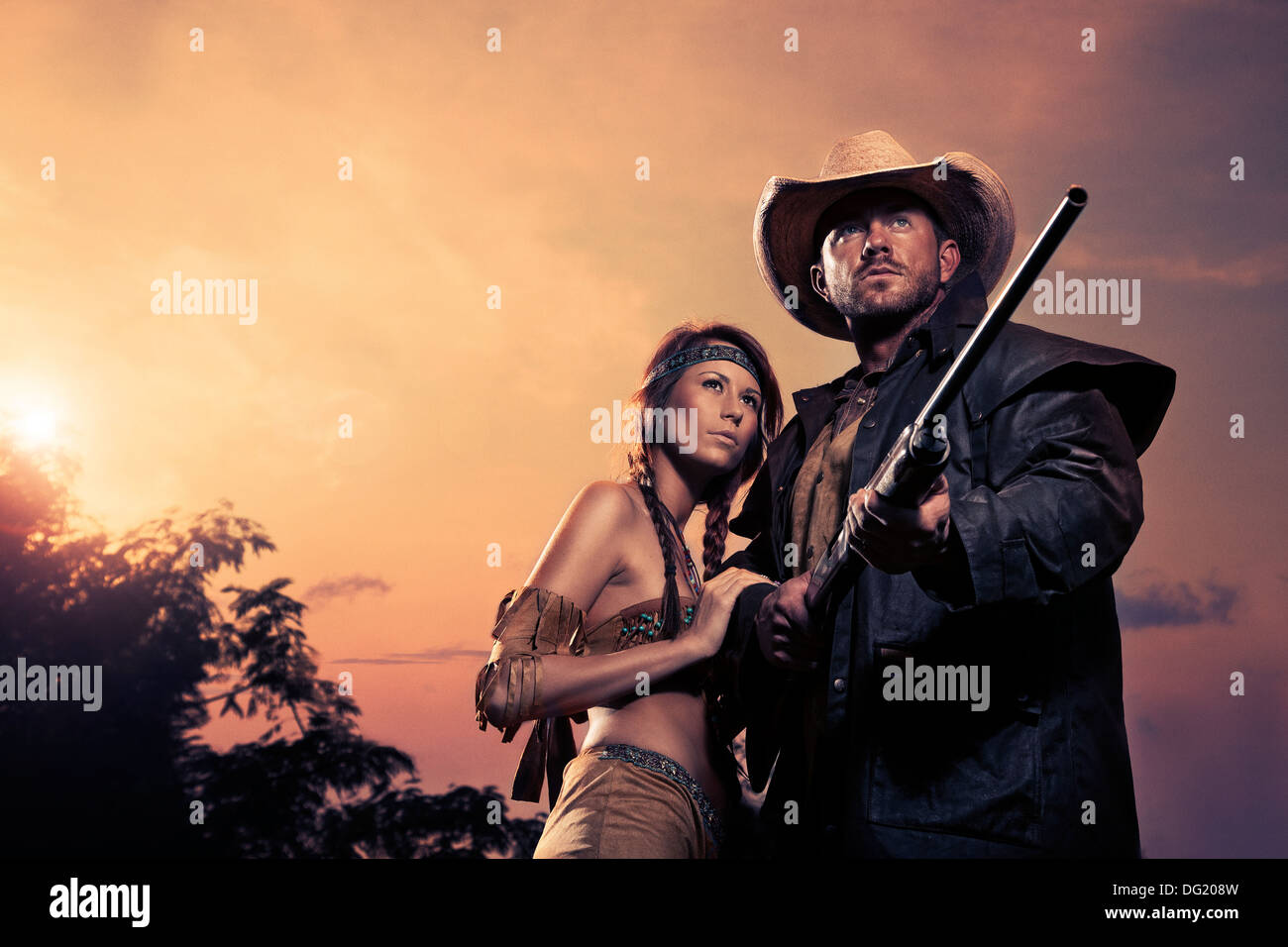 Cowboy and Indian woman with rifle in front of sundown - Stock Image