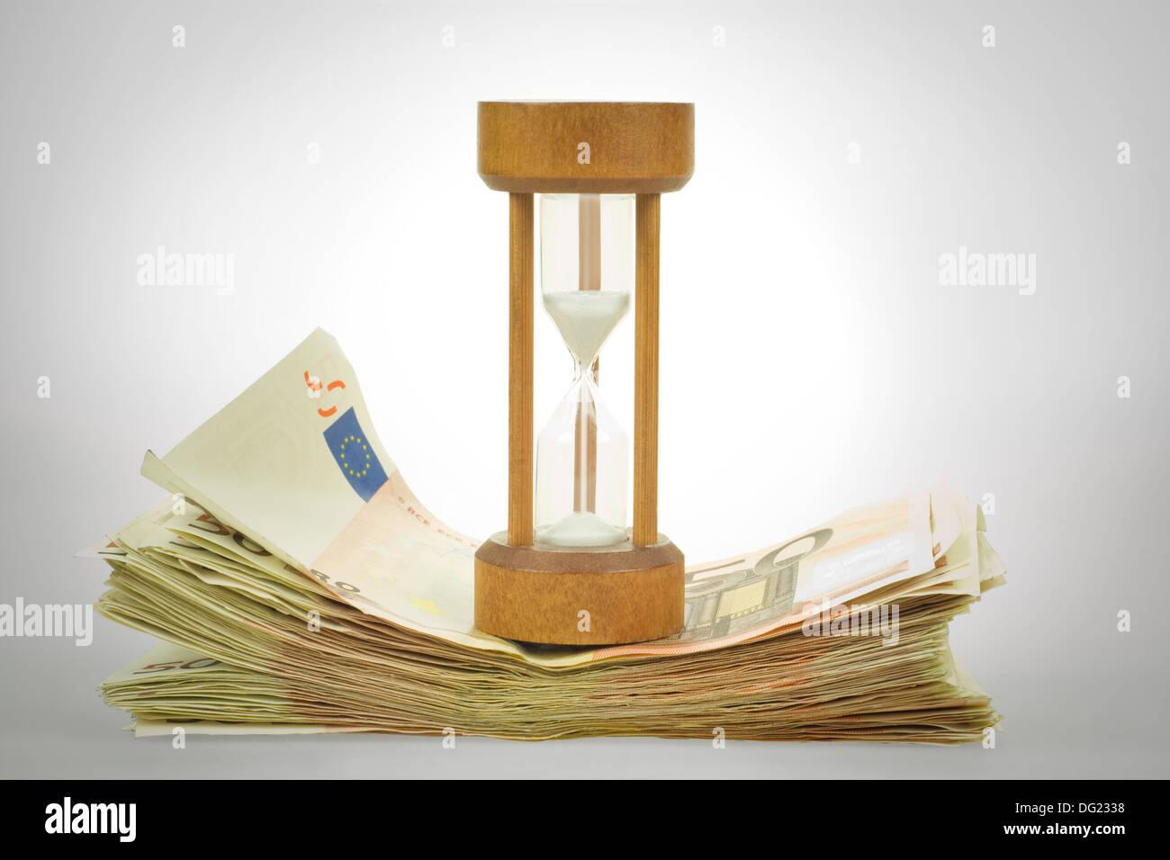 sandglass on wad of fifty euros bills - Stock Image