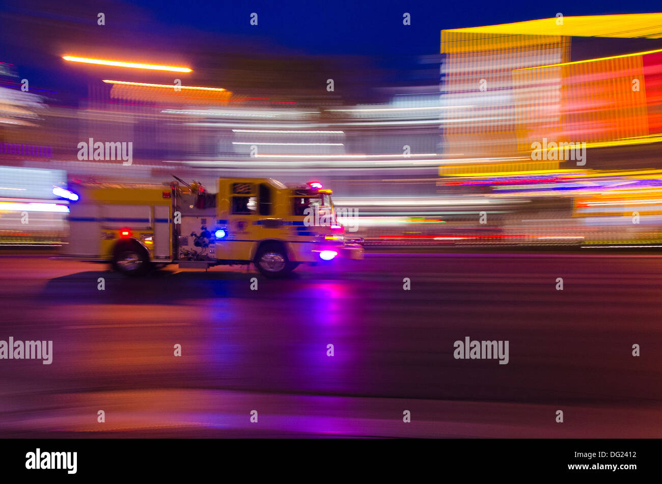 Firetruck rushes to an an incident along Las Vegas Boulevard with significant motion blur against a night sky background of illuminated buildings - Stock Image