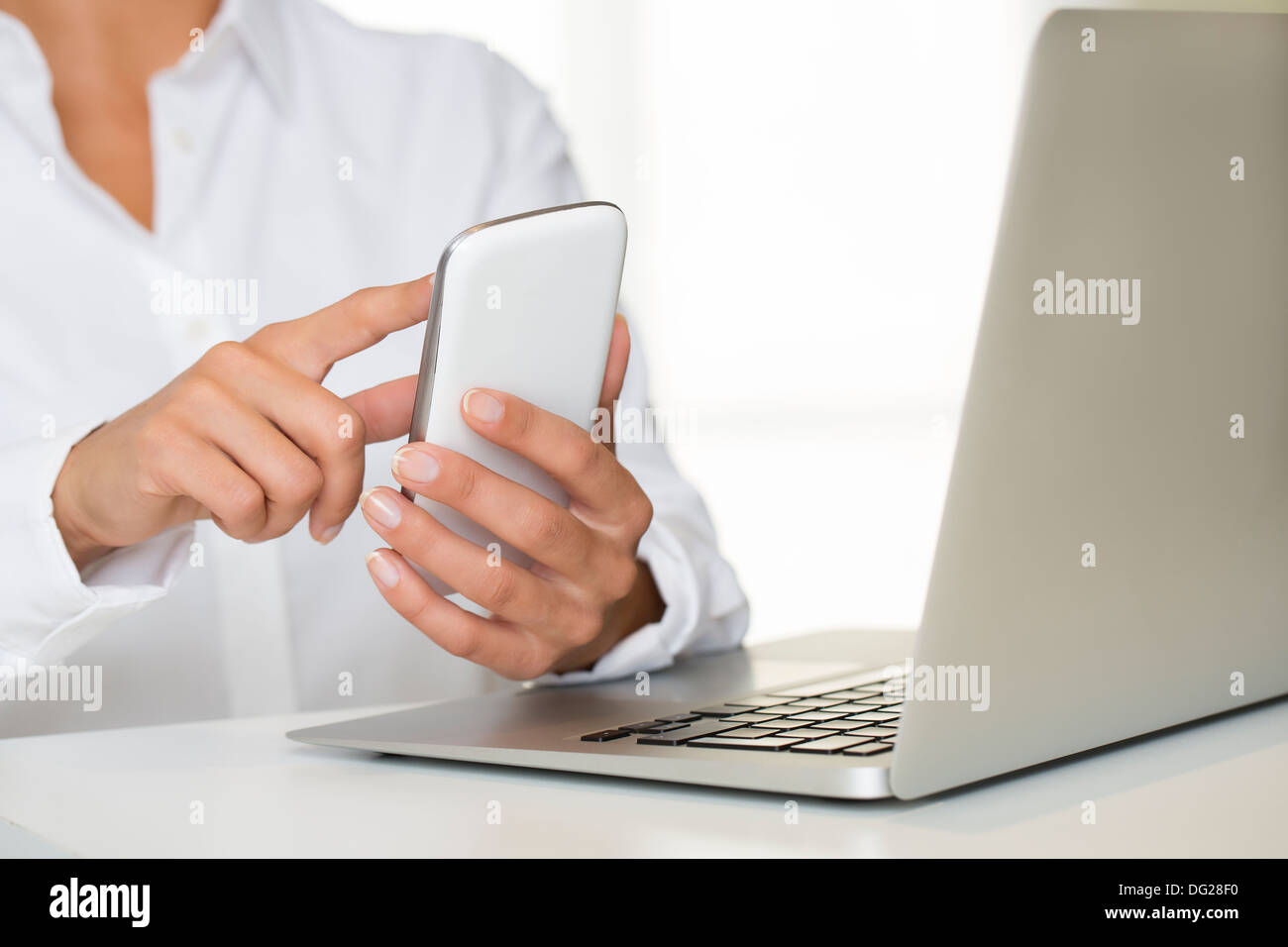 Female laptop cell phone finger table desk indoor - Stock Image