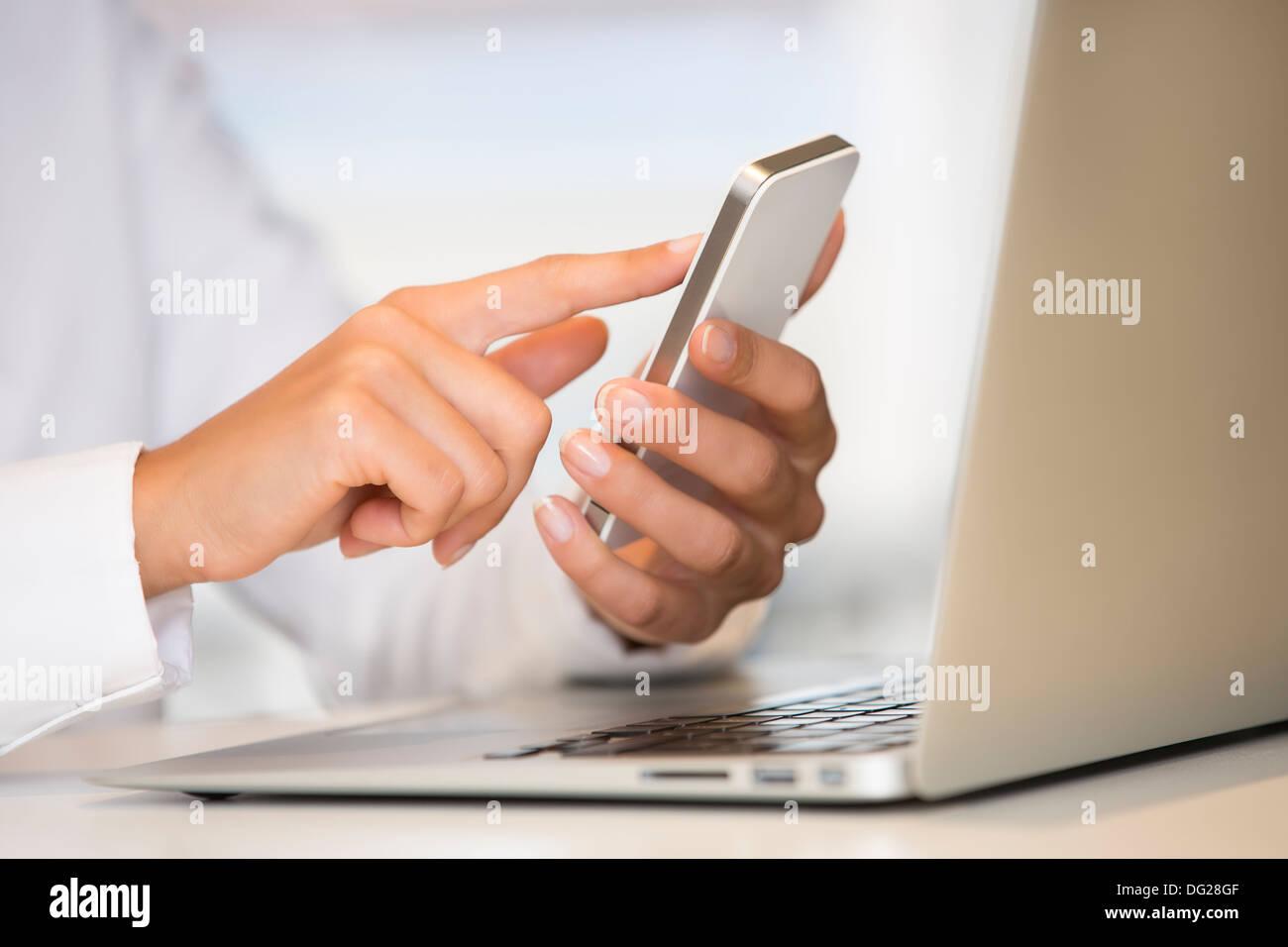 Female laptop cell phone finger table desk indoor - Stock Image