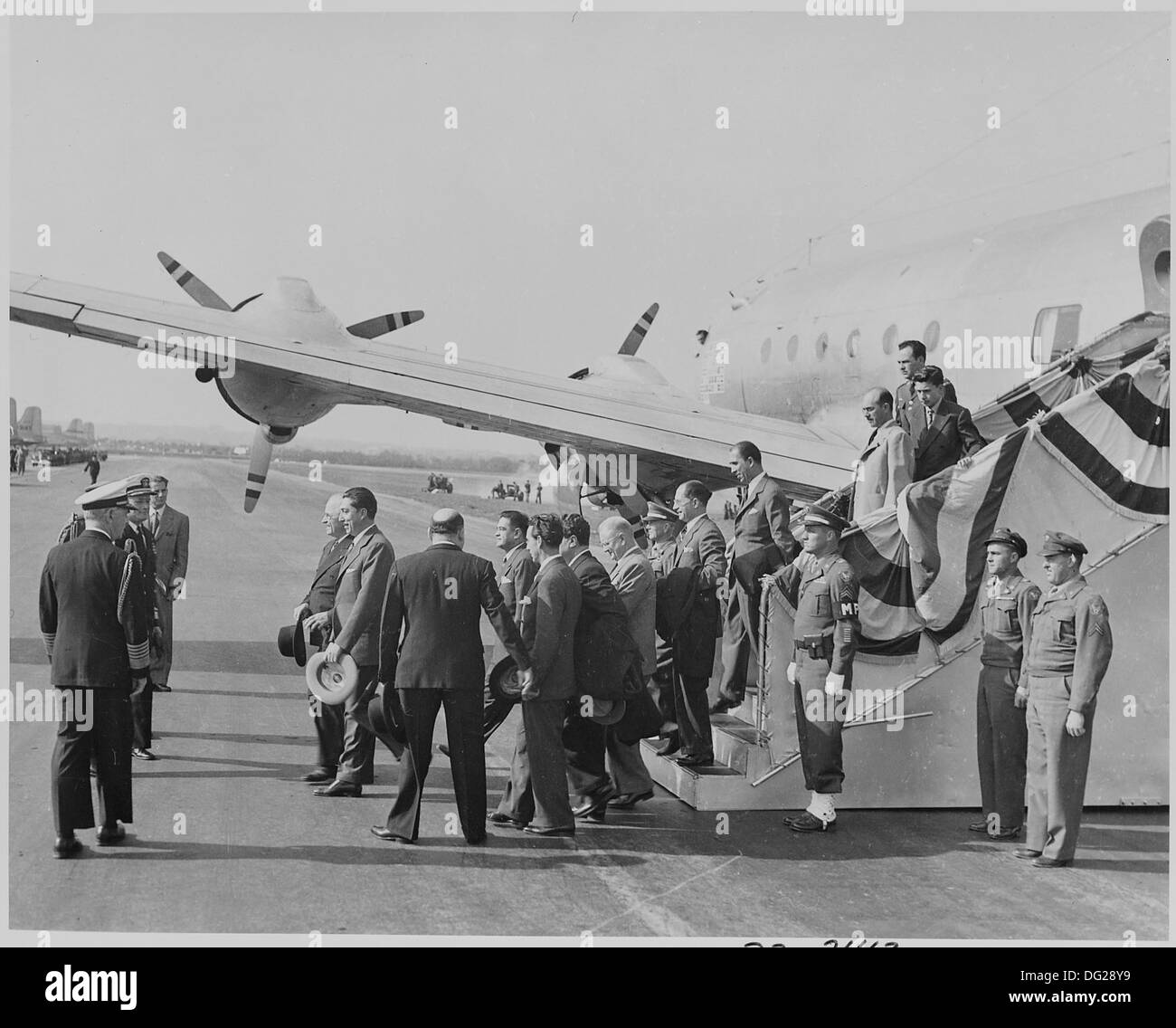 Photograph of Mexican President Miguel Aleman walking from his airplane at Washington's National Airport, accompanied... 199572 - Stock Image