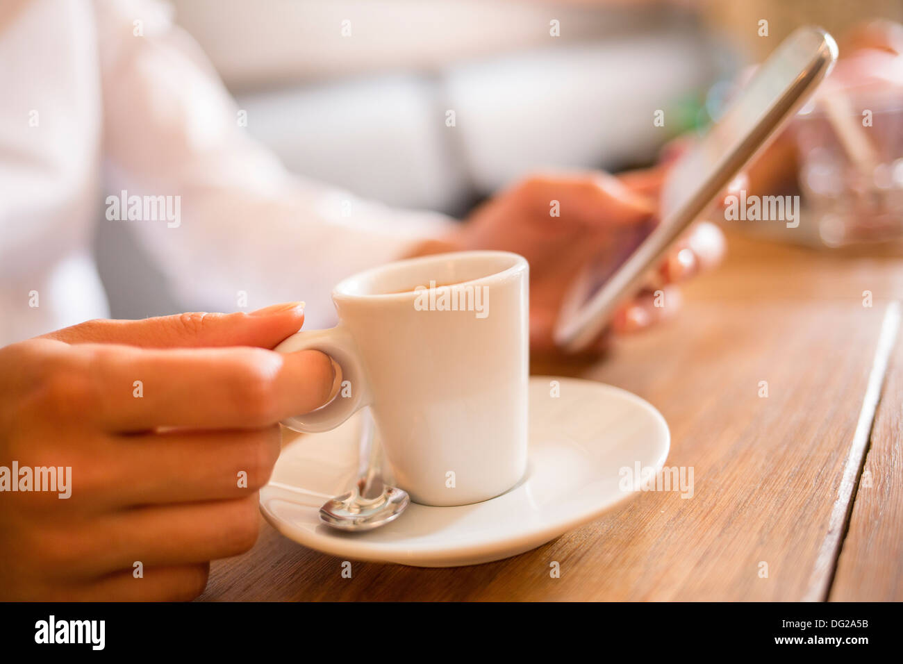 Female message sms mobile phone cafe - Stock Image