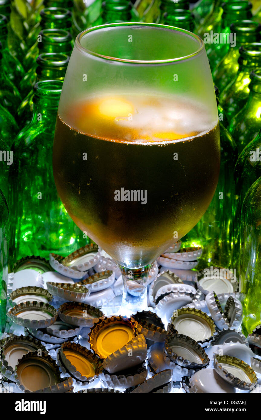 Glass of beer with empty bottles and caps - Stock Image
