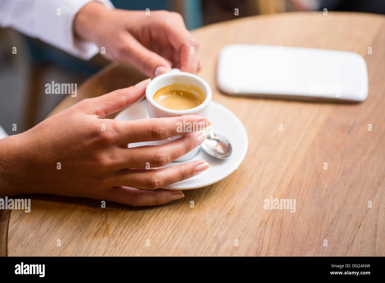 Female restaurant hand coffee table mobile phone - Stock Image
