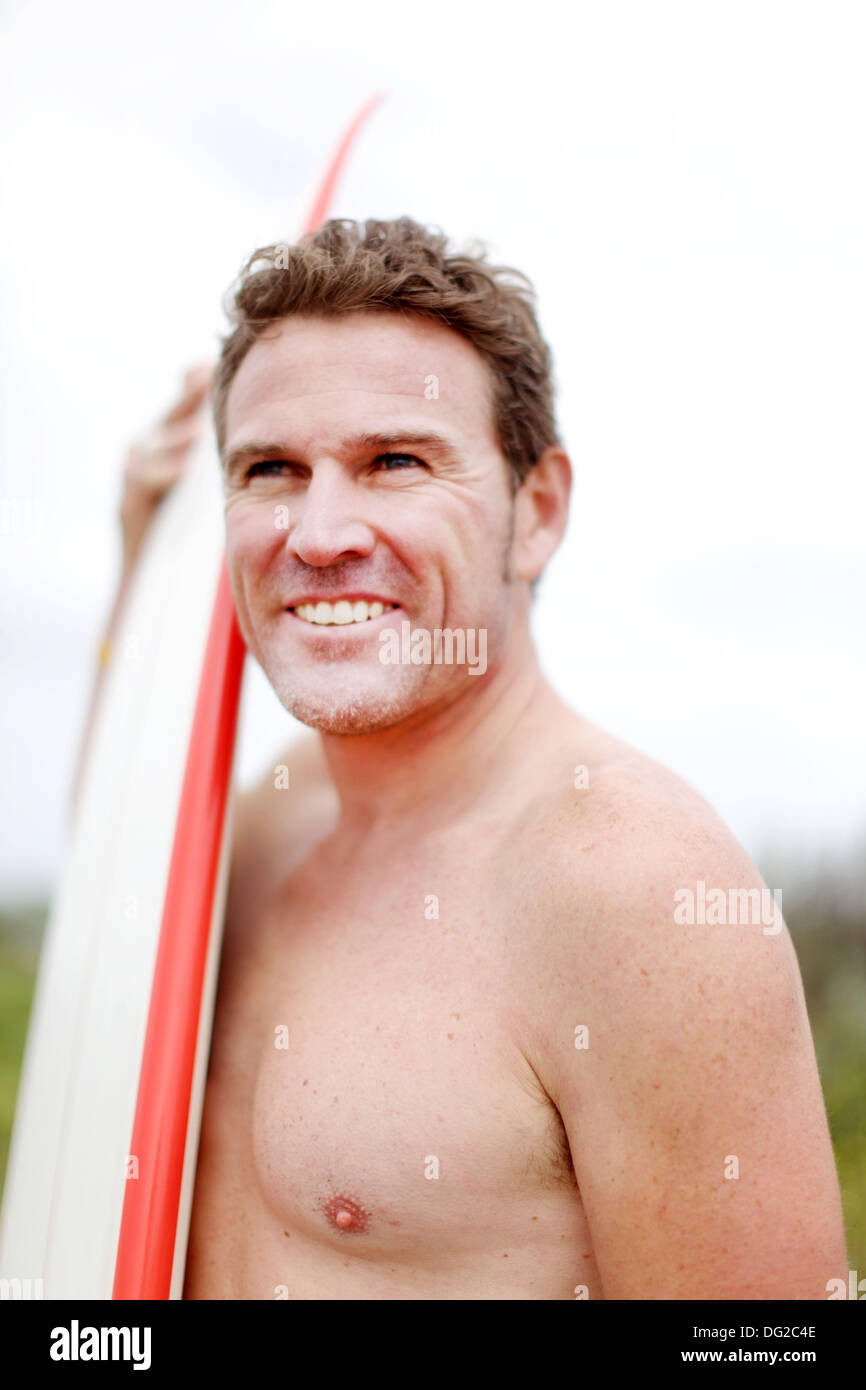 Torquay, Victoria, Australia. 12th Oct, 2013. A surfer waxes his board and checks the surf before heading into the water near Torquay in Victoria. © Marianna Massey/ZUMAPRESS.com/Alamy Live News - Stock Image