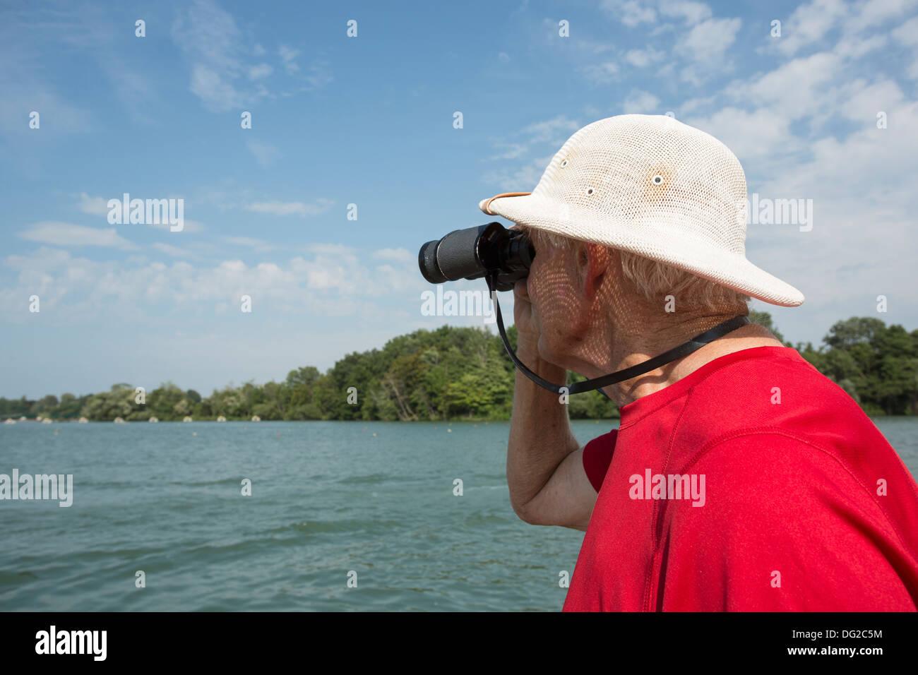 older gentleman looking through binoculars against the sky - Stock Image