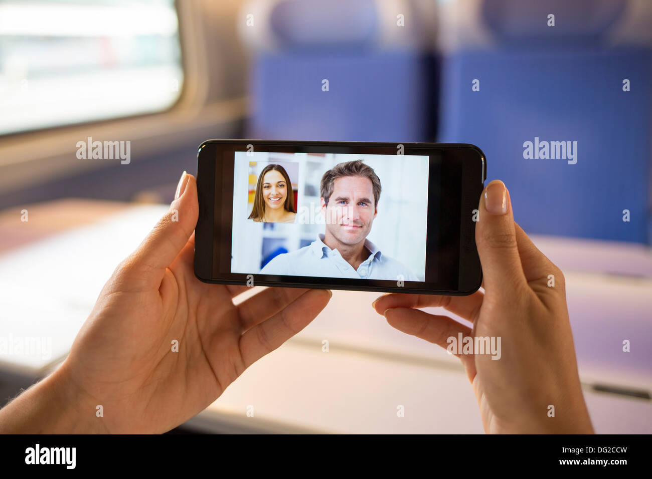 Woman in train chatting on her mobile phone. Video conference - Stock Image