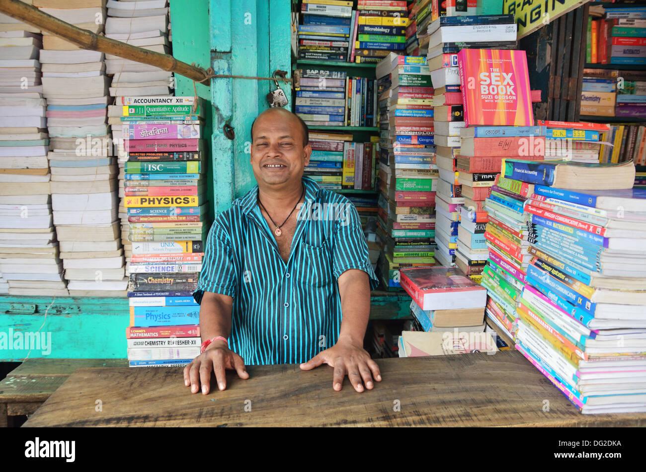 Book seller smiles inside of his shop in College Street in Kolkata, India - Stock Image