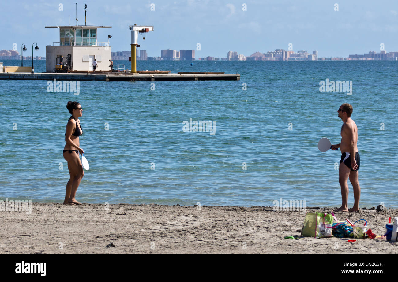 A young couple playing with a bat and ball on the beach in Los Alcazares Murcia Spain mar menor - Stock Image