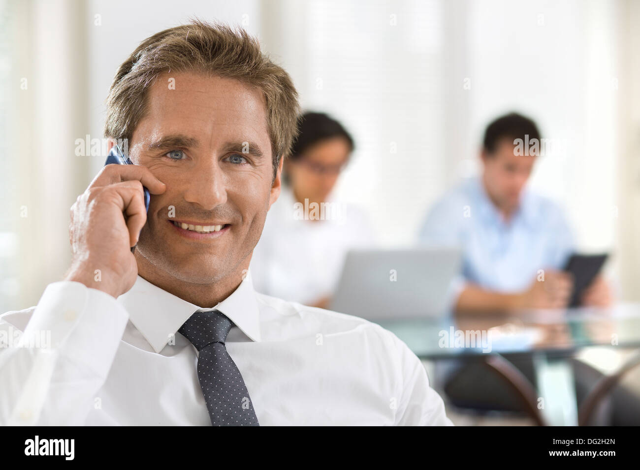 Male mobile phone office desk looking camera Stock Photo