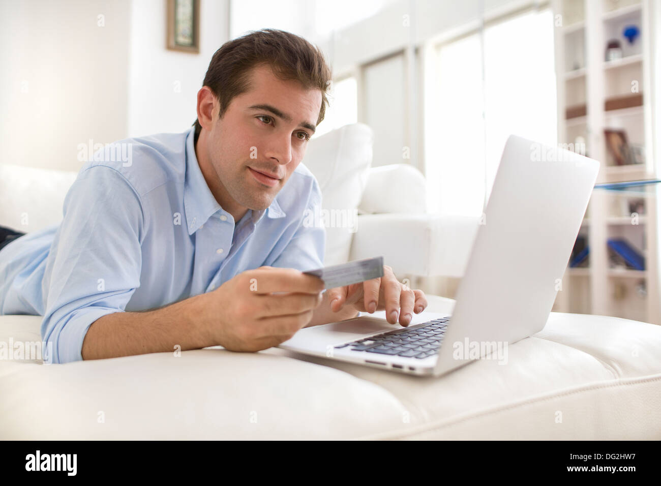 Male couch sofa indoor computer internet - Stock Image