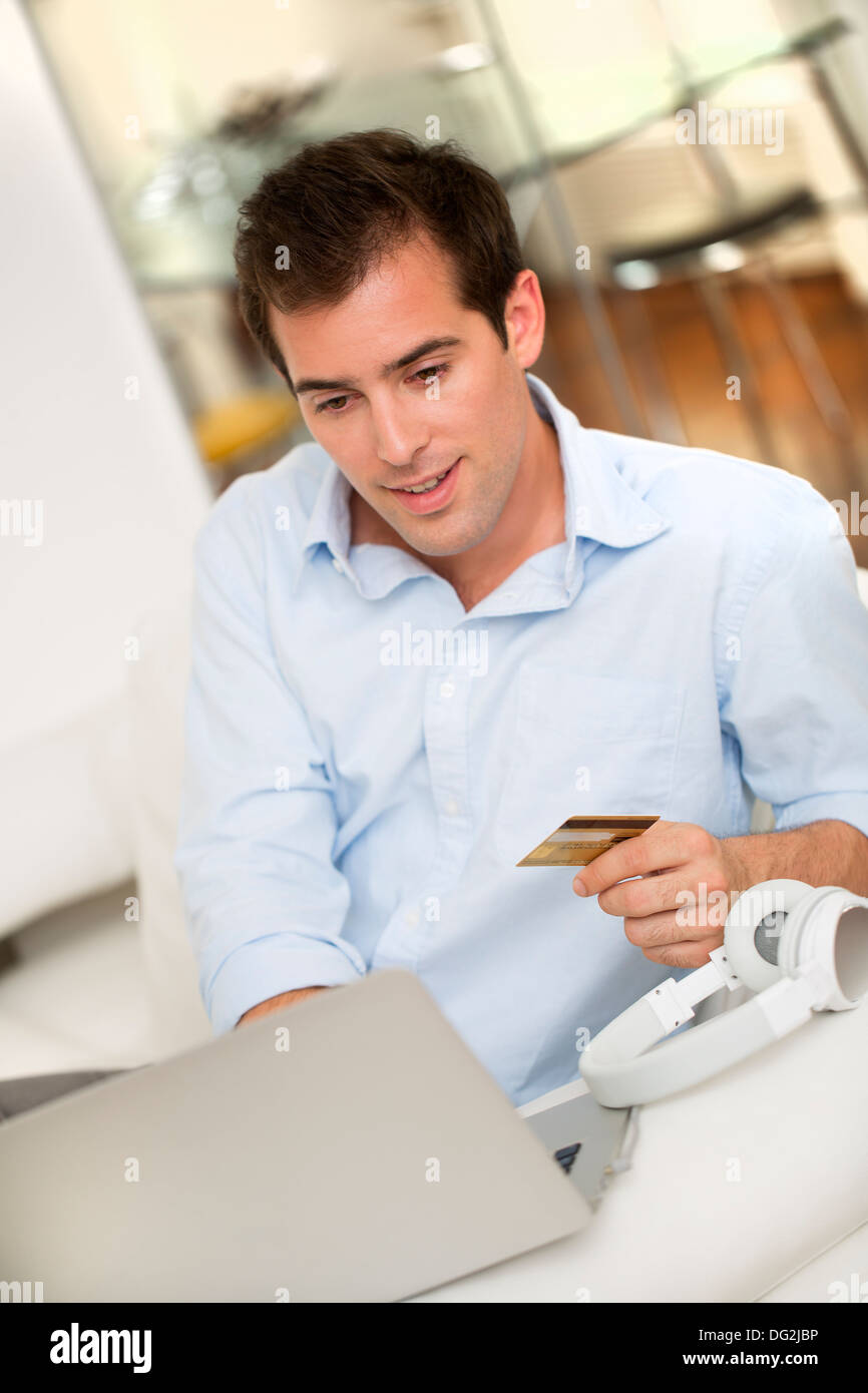 Male laptop credit card music indoor - Stock Image