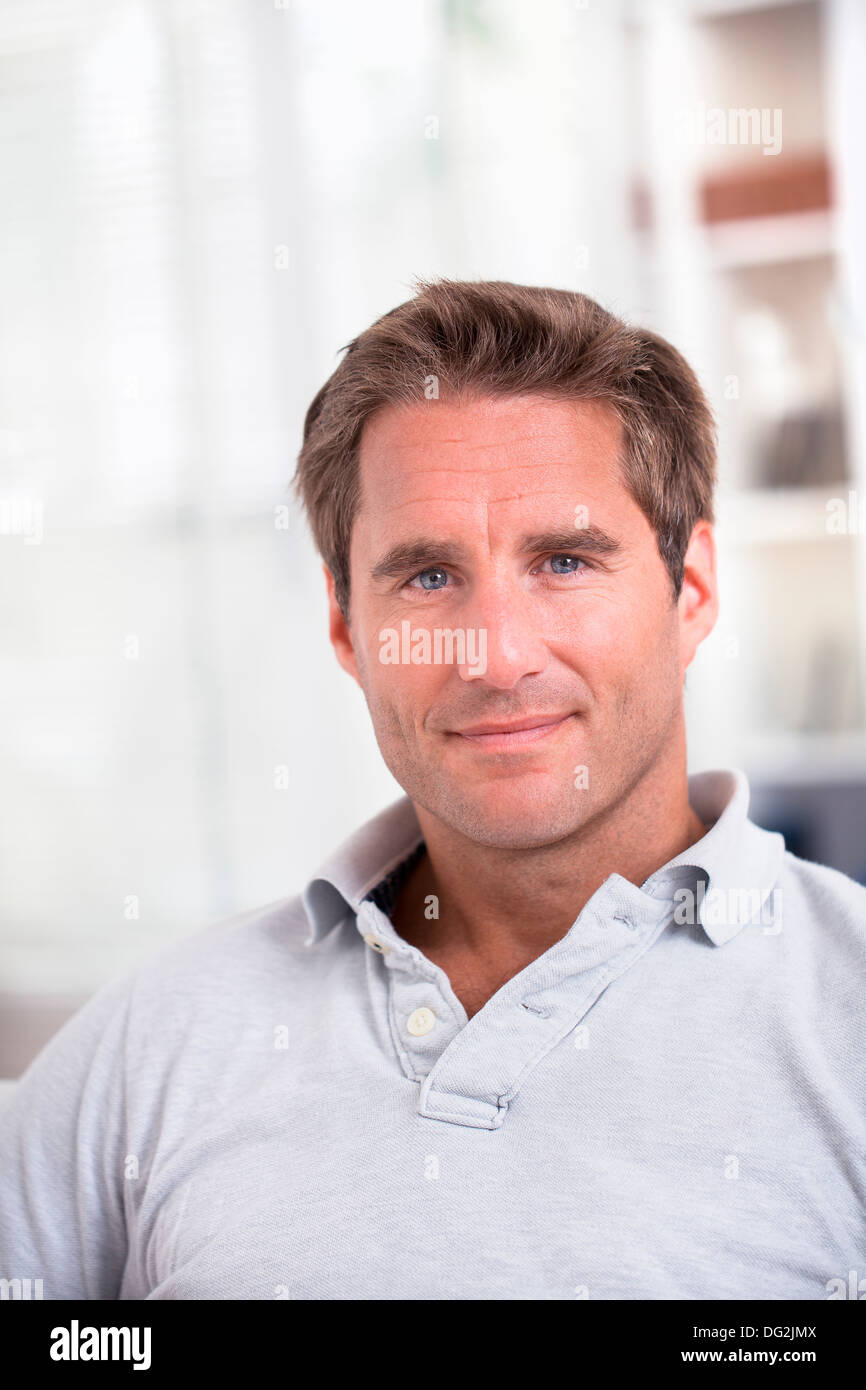 Male Sitting On Sofa Relaxing At Home Looking To Camera Smiling - Stock Image