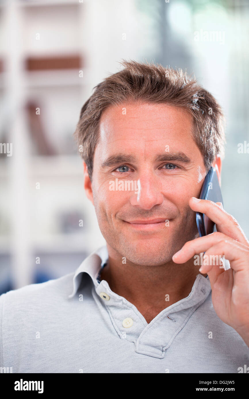 Happy mature male talking on mobile phone indoor - Stock Image