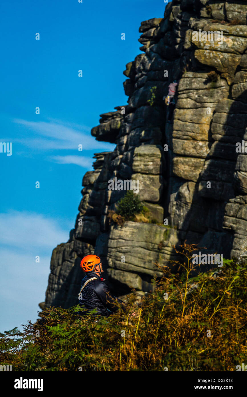 Climber deliberating over Flying Buttress Direct at Stanage, Peak District, UK - Stock Image