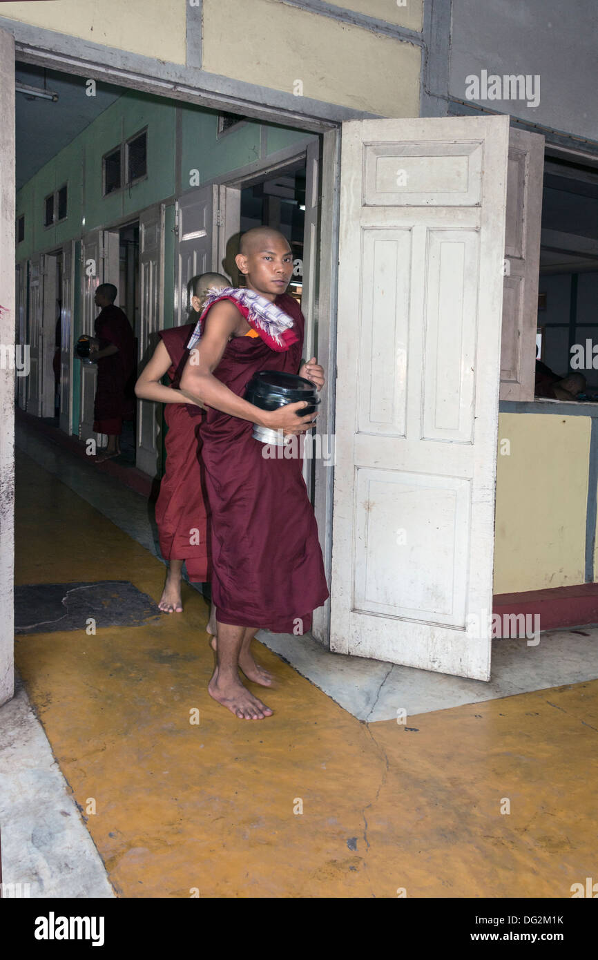 Monks hurrying to the dining hall with their midday meal, Mahagandayon Monastery, Amarapura, Myanmar - Stock Image