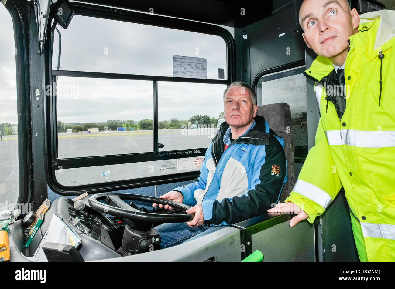 A trainee receives instruction from a bus driving instructor - Stock Image