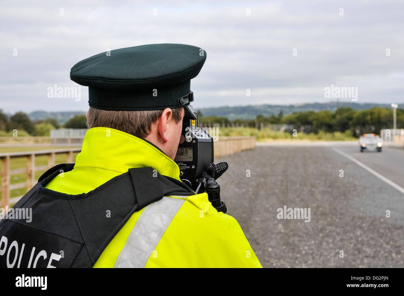 Police officer uses a Laser Technology Inc UltraLyte laser speed detector gun - Stock Image