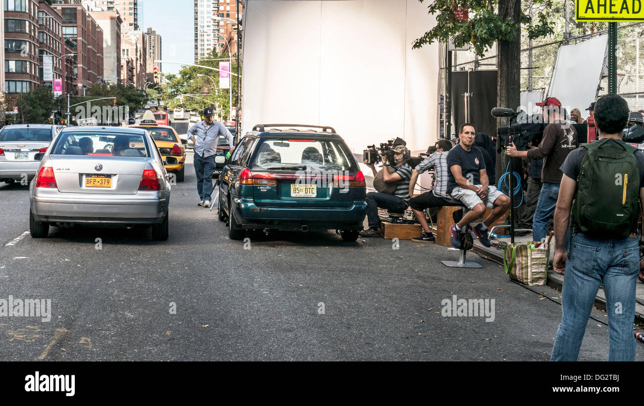 cameraman shooting into car as traffic is rerouted on 10th Avenue & a new Annie (remake of 1982 movie musical) films in New York City, Oct. 12, 2013. The revival of the original 1977 Broadway musical is currently playing on Broadway, very near this location in Hells Kitchen. The film stars Quvenzhane Wallis & Jamie Foxx. - Stock Image