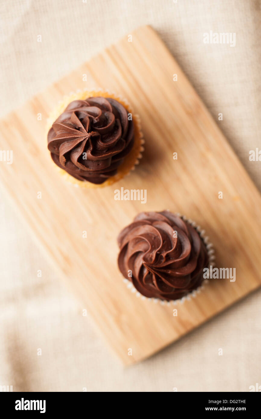 Two Cupcakes with Chocolate Icing on Wood Cutting Board, High Angle View - Stock Image