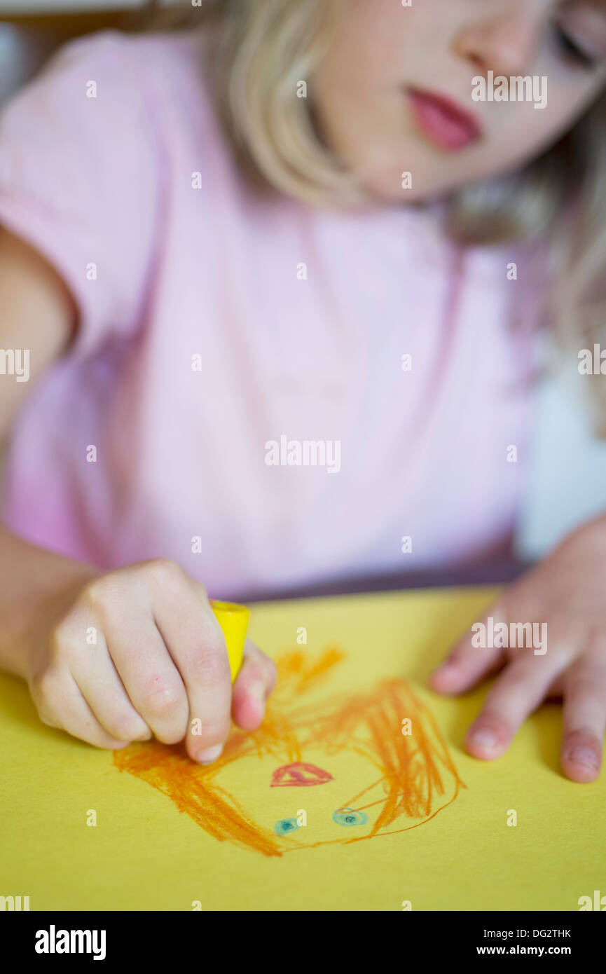 Young Girl Drawing on Yellow Paper - Stock Image