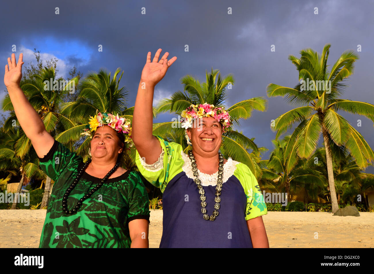 Portrait of two happy mature Polynesian Pacific islanders women on tropical beach with palm trees in the background. - Stock Image