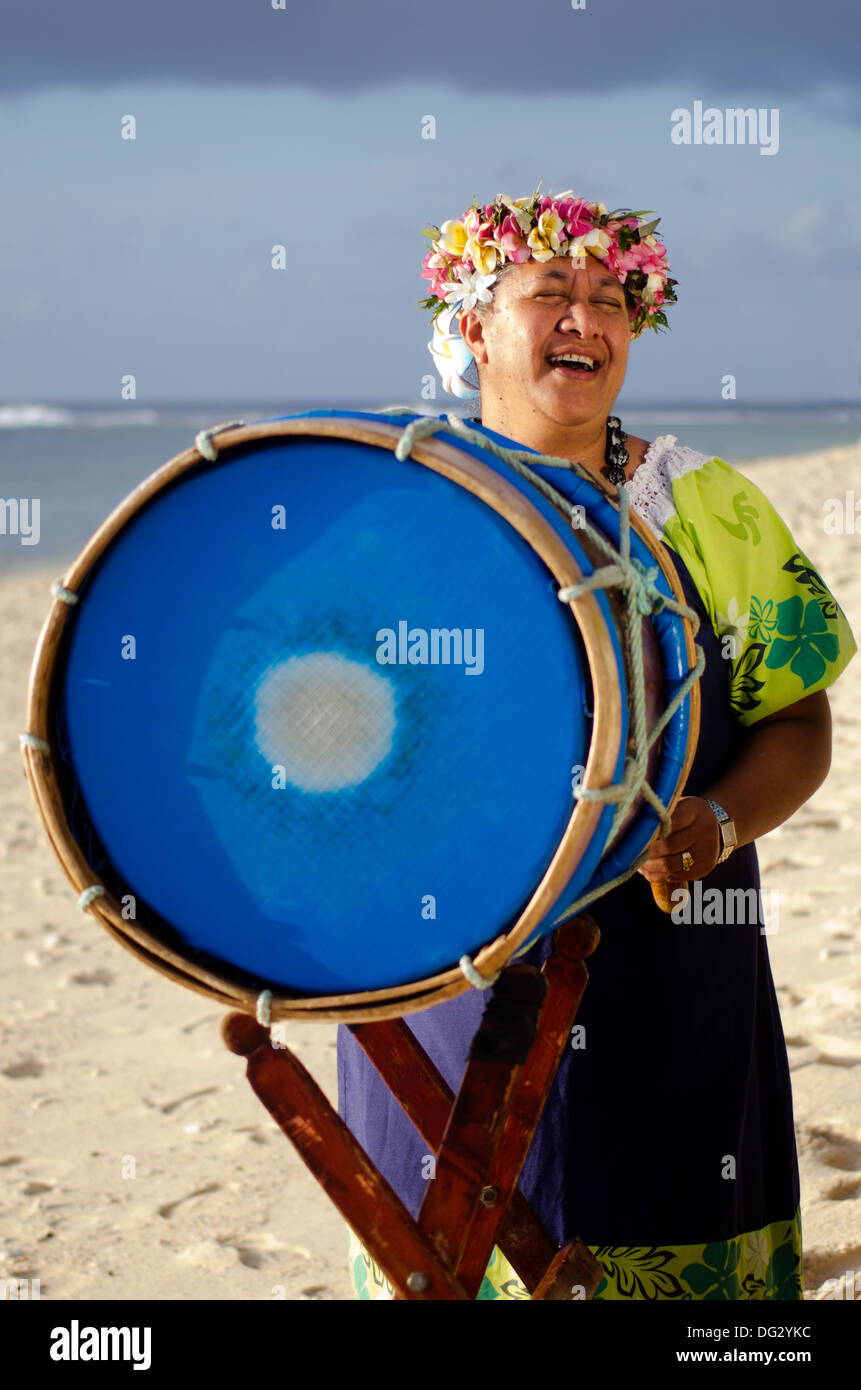 Portrait of mature Polynesian Pacific islanders woman sing and plays Tahitian Music with drum on tropical beach. - Stock Image