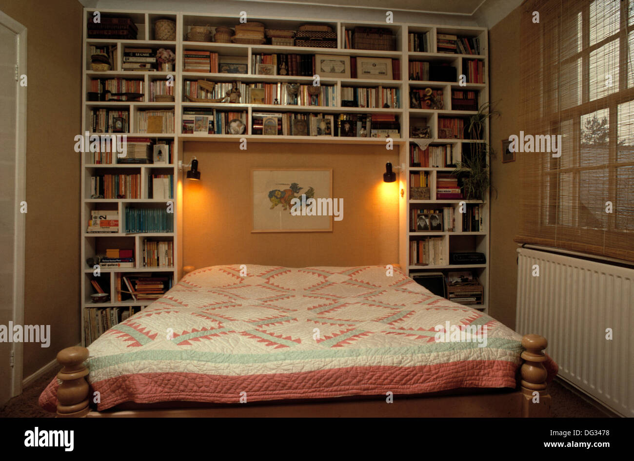 fitted bookshelves beside and above bed with patchwork quilt in townhouse bedroom with spotlights in alcove - Bookshelves Around Bed