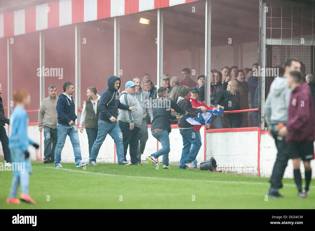 Atherstone, Warwickshire, UK. 12th October, 2013. A group of fans from the home end of the Sheepy Road ground walk around the perimeter of the pitch and scale the fences to attack the visiting supporters (Barrow AFC). A firework was also thrown towards to the terrace of the away following. A flag was stolen from the Barrow AFC fans and then set on fire using a lit firework. Atherstone chairman Rob Weale apologised for what occurred and vowed to pursue the perpetrators. - Stock Image