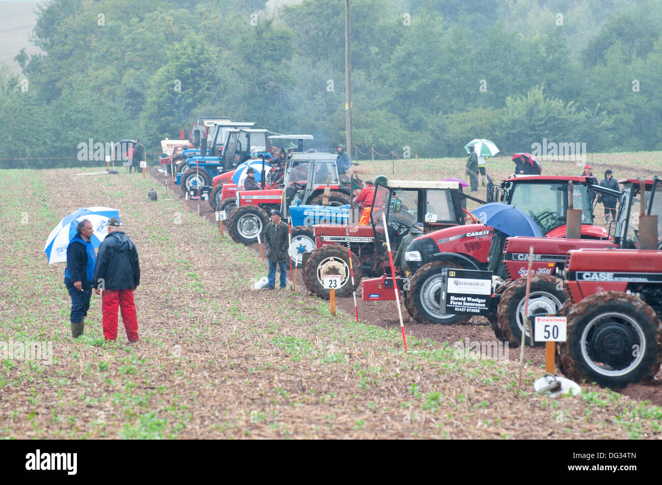 Llanwarne, Herefordshire, UK. 13th October 2013. Despite the rain stoicism and competitive spritit is evident on the second day of the 2013 British National Ploughing Championships which have returned to Herefordshire for the first time in 27 years. The top ploughmen of  each class (reversible and conventional) will represent Britain at the World Ploughing Championships to be held in France in 2014. Photo credit: Graham M. Lawrence/Alamy Live News. - Stock Image
