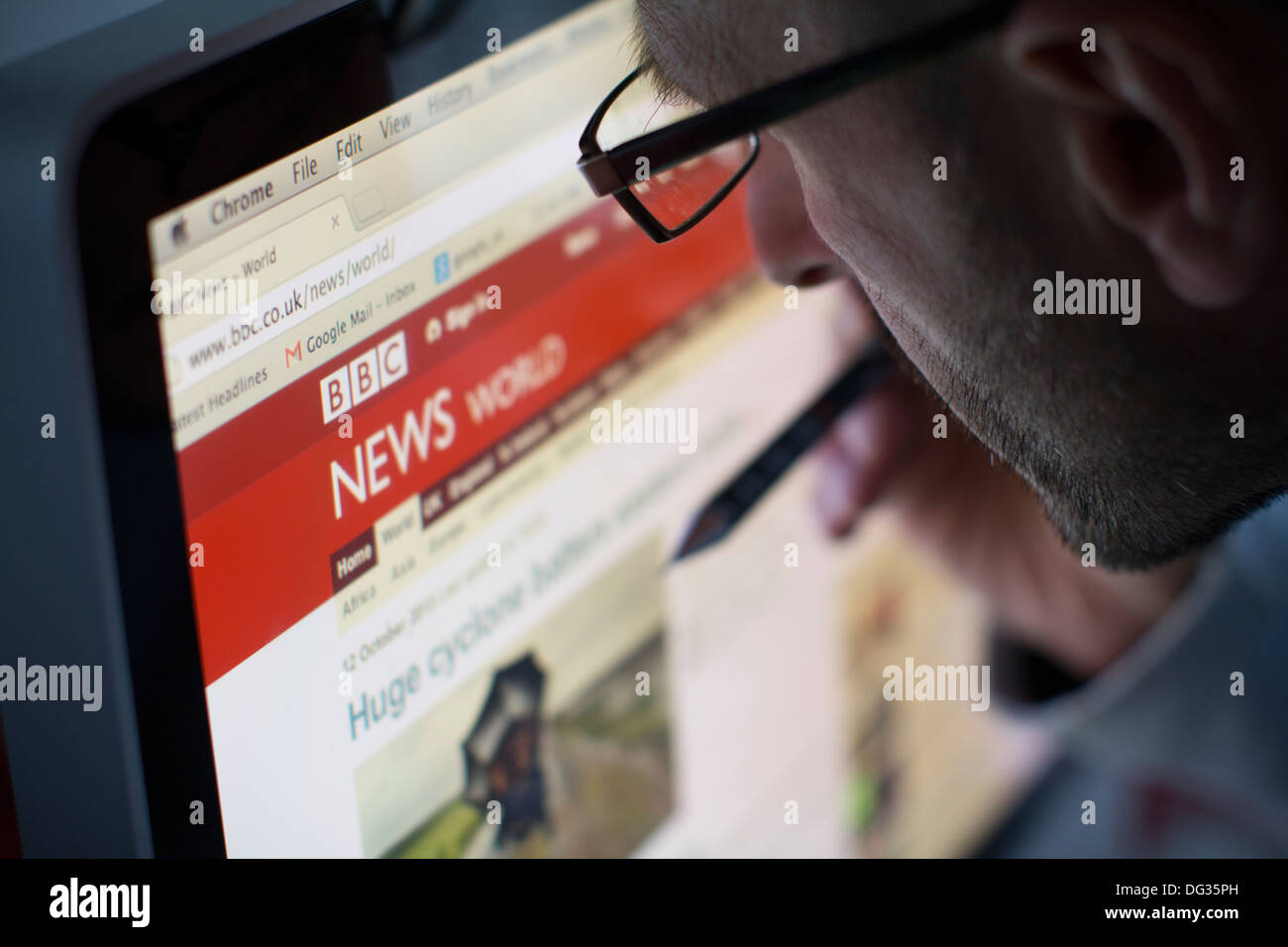 Adult male looking at the online internet website of bbc news - Stock Image