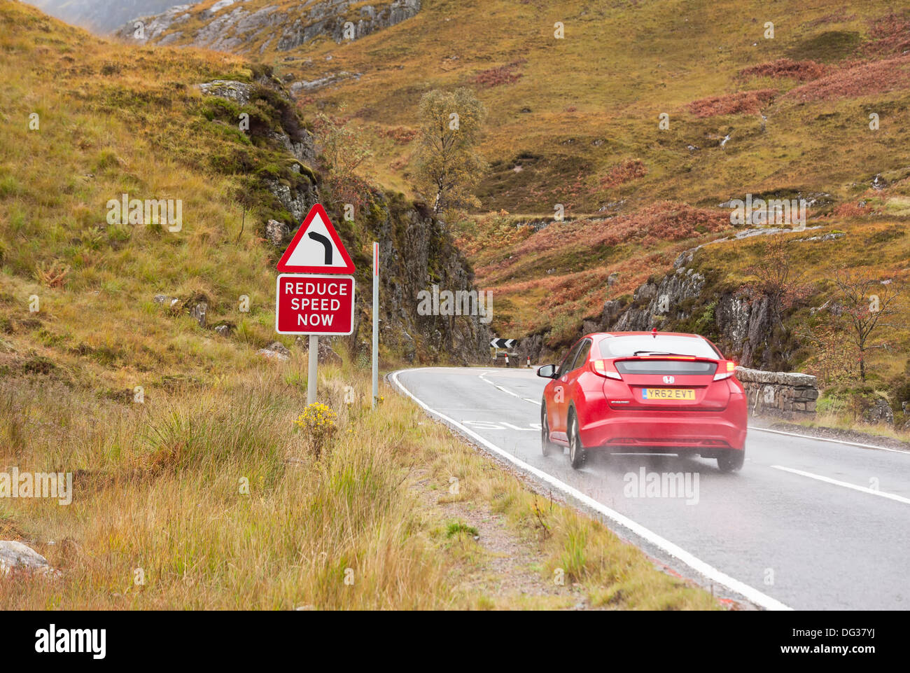 A car braking hard on the wet road conditions at a reduce speed now sign on the A82 at glencoe in the scottish highlands - Stock Image