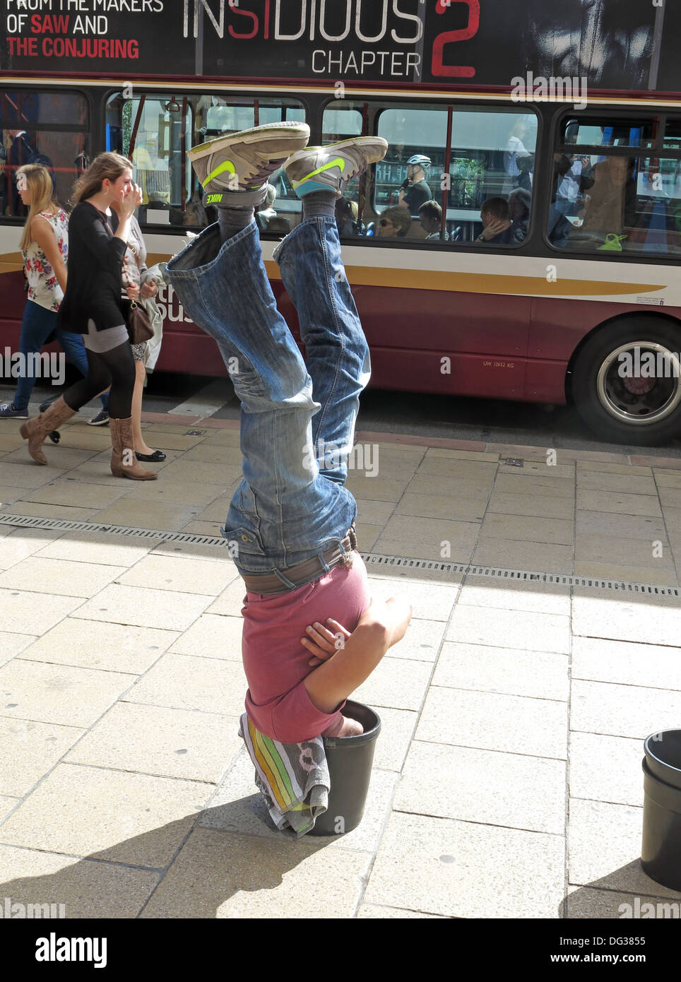 Busker in Princes st Edinburgh upside down in a bucket Scotland UK - Stock Image
