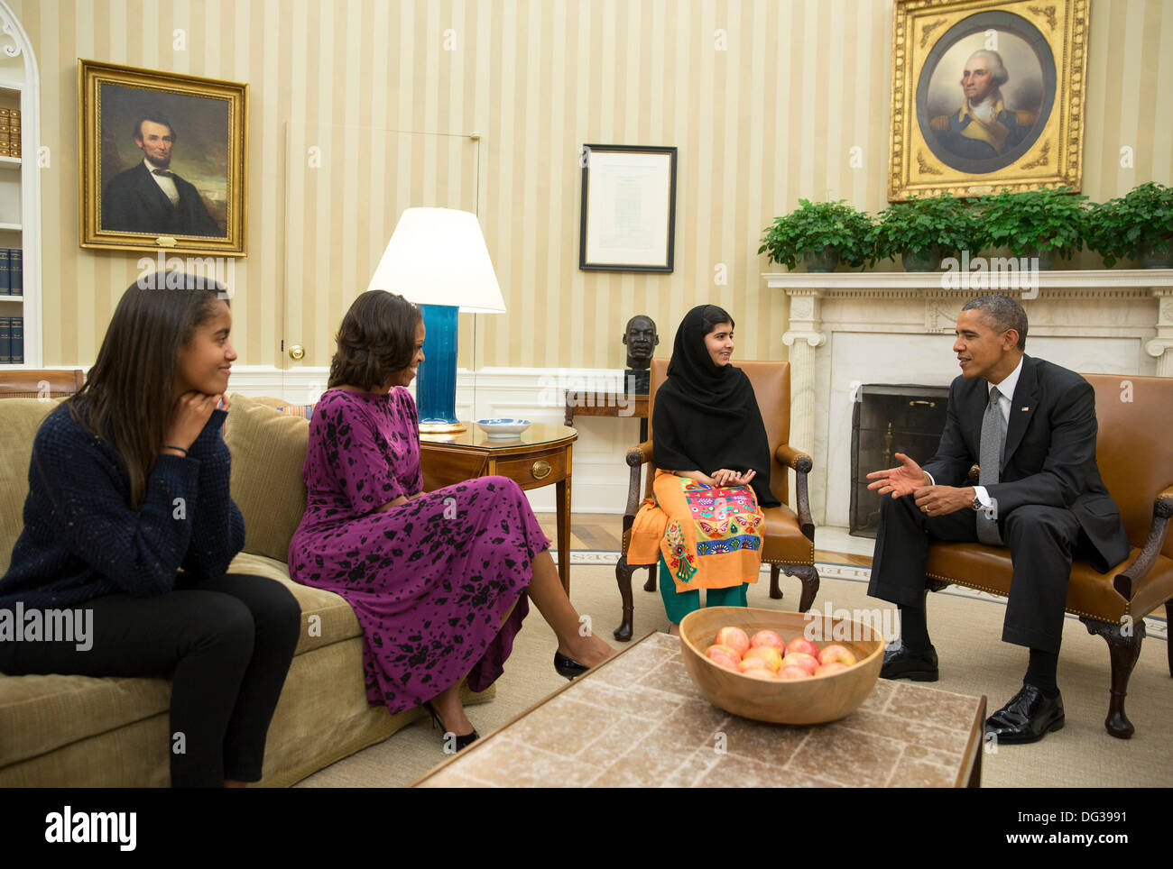 US President Barack Obama, First Lady Michelle Obama, and their daughter Malia meet with Malala Yousafzai, the young Pakistani schoolgirl who was shot in the head by the Taliban a year ago in the Oval Office of the White House Oct. 11, 2013 in Washington, DC. - Stock Image
